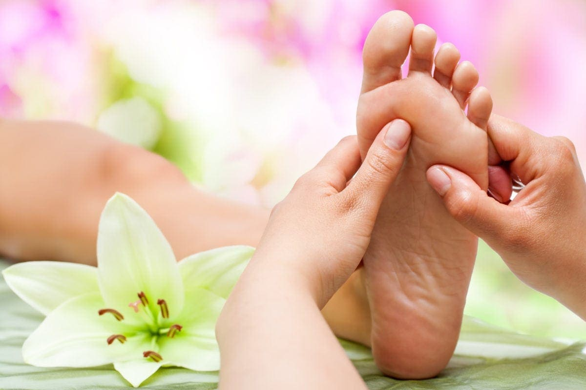 Close up of therapist's hands massaging female foot.